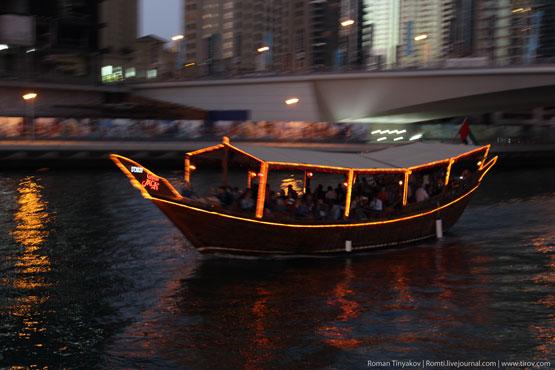 Пролетающая мимо лодка в заливе Dubai Marina с флагом ОАЭ