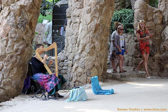 Женщина играет на арфе в парке Гуэль
