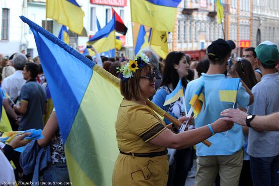 Женщина вручает флаг Украины прохожим