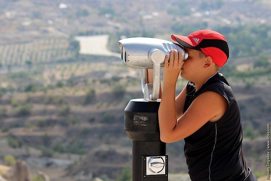 Сын рассматривает долину Каппадокии в телескоп-бинокль