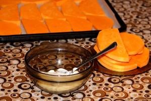 Тарелка с мёдом и сметаной на фоне кусочков тыквы