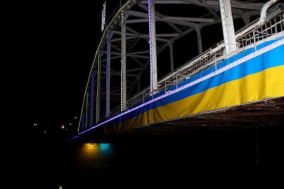 Флаг Украины на весь мост с гербом по центру и соответствующей подсветкой под мостом