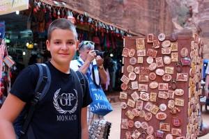 Алексей на фоне магазина сувениров и магнитов с изображением города Петра