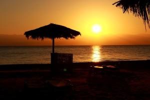 Красивый восход солнца из-за гор Иордании отснят с пляжа в Египте у Красного моря