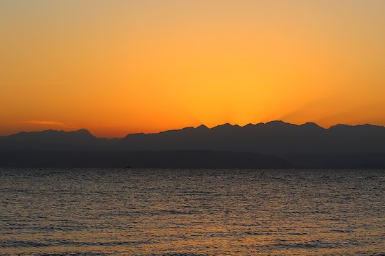 Солнечные лучи восходящего солнца над Красным морем из-за гор Иордании