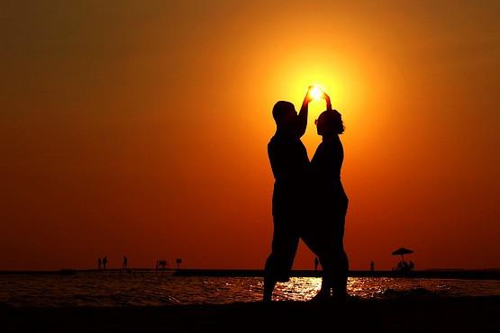 Пара с солнцем в руках на закате