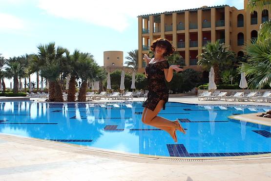 Танюшка в полёте на фоне бассейна, пальм и отеля в Египте