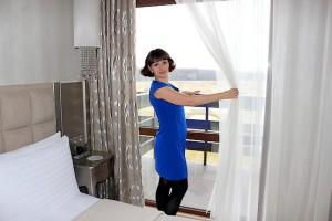 Таня у окна в номере отеля
