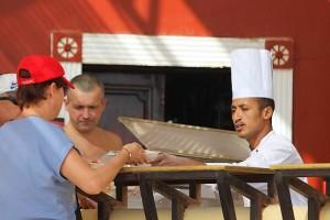 Повар угощает пиццей в ресторане