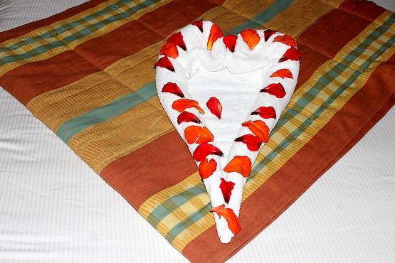 Сердце из полотенца на кровати