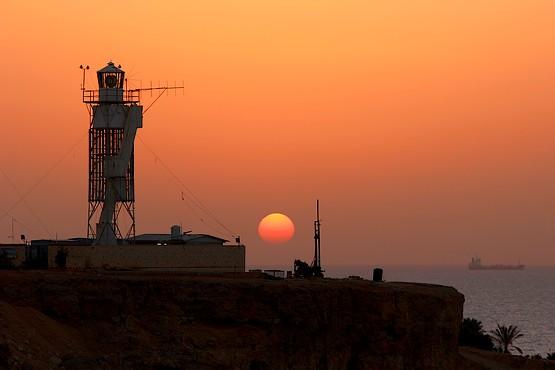 Восход солнца на фоне маяка и корабля в Красном море