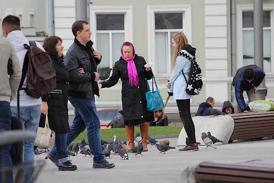 Женщина, подкармливающая голубей