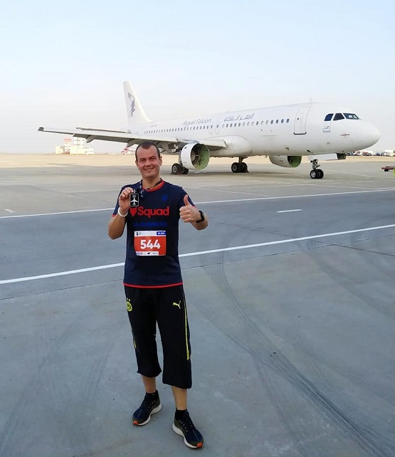С медалью пробега на фоне самолёта