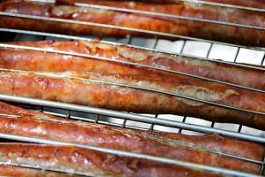 Колбаски готовятся на мангале